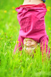Happy little girl standing upside down on grass in summer park Stock Photography