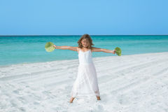 Happy little girl standing on white sand tropical beach Royalty Free Stock Images