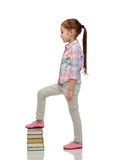 Happy little girl stepping on book pile Stock Photo