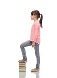 Happy little girl stepping on book pile Stock Photography