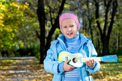 Happy little girl strumming a toy guitar Stock Photo