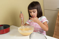 Happy little girl sucking the mixture to cook a cake. Happy little girl sucking with finger the mixture to cook a cake Stock Photography