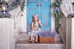 Happy little girl in a summer colorful dress sits on the porch