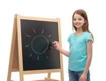Happy little girl with sun drawn on blackboard Stock Photos