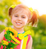 Happy little girl with sunflowers Stock Images