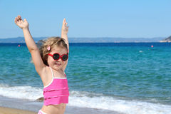 Happy little girl with sunglasses and hands up Stock Photo