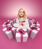 Happy little girl surrounded by gifts pink Stock Photo