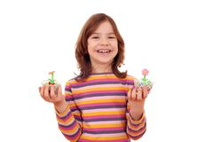 Little girl with sweet cupcakes decorated as spring flowers. Happy little girl with sweet cupcakes decorated as spring flowers stock image