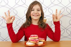 Little girl with sweet donuts and ok hands signs Royalty Free Stock Photos