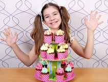 Little girl with sweet muffins and hands up Stock Images
