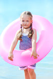 Happy little girl and swim ring at the beach Stock Image