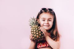 Happy little girl in swim suit holding pineapple. royalty free stock photography