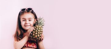 Happy little girl in swim suit holding pineapple. Happy vocations concept, Trendy colors, eco food. Copy space for text stock photo