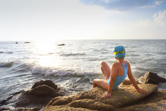 Happy little girl swimmer at the beach. Happy little girl in a bathing suit, swim cap, goggles at the beach Stock Photo