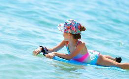 Happy little girl swimming on the bodyboard stock images