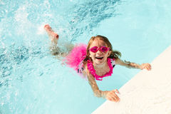 Happy little girl swimming holding on to pool edge. Portrait of happy little Caucasian girl wearing goggles swimming holding on to pool edge, looking at camera Stock Images
