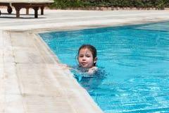 Little girl swimming in a pool. Happy little girl swimming in a pool Royalty Free Stock Photos