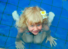 Happy little girl  in a swimming pool. Looking at the camera smiling Royalty Free Stock Images