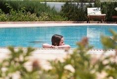 Little girl swimming in a pool. Happy little girl swimming in a pool Royalty Free Stock Images