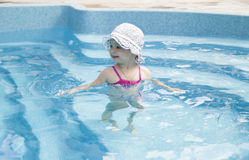 Happy little girl in swimming pool Stock Photos