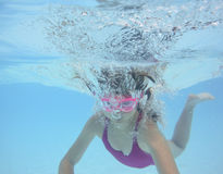 A happy little girl swimming in a pool Stock Photo