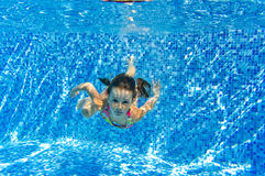 Happy little girl swims underwater in pool Stock Image