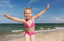 Happy little girl in swimwear having fun on beach Stock Photos
