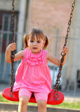 Happy little girl on a swing Royalty Free Stock Photos