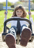 Happy little girl on a swing Stock Image