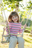 Happy little girl on a swing. In the park royalty free stock image