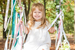 Happy little girl on a swing. Child, Playing, Playground. Happy little girl on a swing stock photo