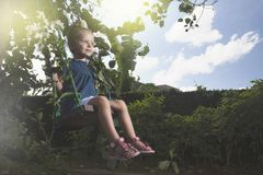 Happy little girl swing on Children`s Day or Mother`s Day. stock image