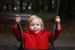 Happy little girl on swing in park Stock Photos