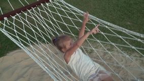 Happy little girl swinging in hammock slow motion stock footage video stock video