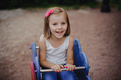 Happy little girl is swinging Stock Photo