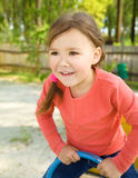 Happy little girl is swinging on see-saw. Cute and happy little girl is swinging on see-saw Stock Photo