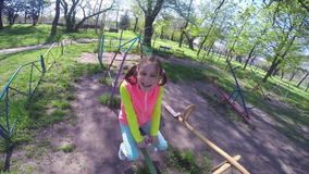 Happy little girl is swinging on see-saw stock footage