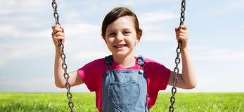 Happy little girl swinging on swing outdoors stock photography