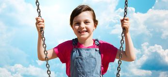 Happy little girl swinging on swing over blue sky Royalty Free Stock Photos