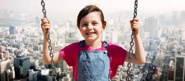 Happy little girl swinging on swing over city Stock Photo