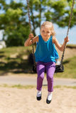 Happy little girl swinging on swing at playground Royalty Free Stock Photo