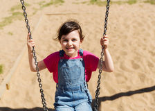 Happy little girl swinging on swing at playground Stock Images