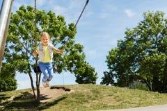 Happy little girl swinging on swing at playground Stock Photo