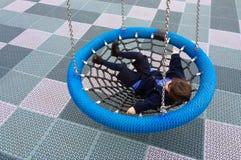 Happy little girl swings on Birds Nest Swing Stock Image