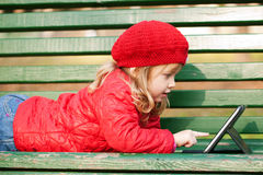 Happy little girl  with tablet pc. Happy little girl wearing red working with tablet pc and lying on bench in the park Royalty Free Stock Photos