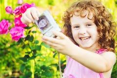 Happy little girl taking self photo on a summer garden. Stock Photos
