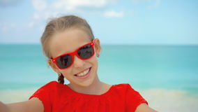 Happy little girl taking selfie at tropical beach on exotic island during summer vacation. Little girl taking selfie portrait with her smartphone on the beach stock video