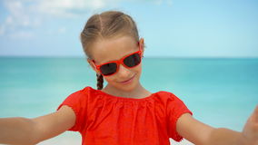Happy little girl taking selfie at tropical beach on exotic island during summer vacation. Little girl taking selfie portrait with her smartphone on the beach stock footage