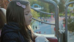 Happy little girl with teddy bear in amusement park on carousel. Pretty girl on family weekend stock footage
