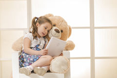 Happy little girl with Teddy bear. Watching her tablet computer Stock Photography